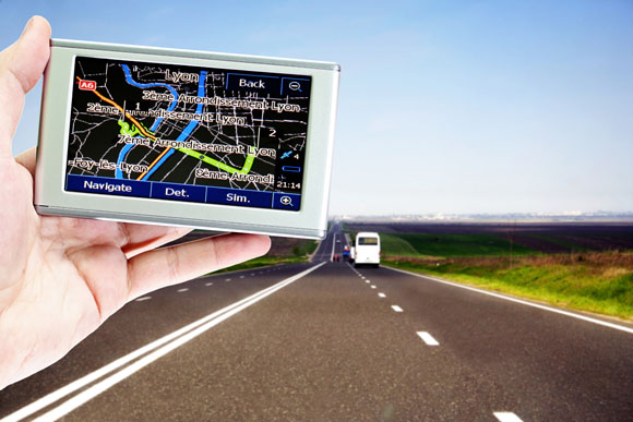 gps in a man hand.  car on the highway